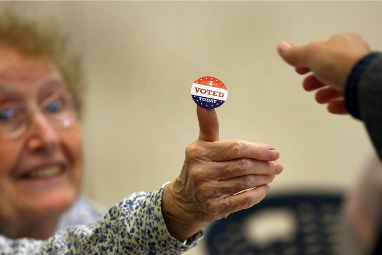 """At the Beech Street Center in Belmont, poll worker Rosemary Good handed out \""""I voted\"""" stickers on Election Day, Nov. 6, 2012."""