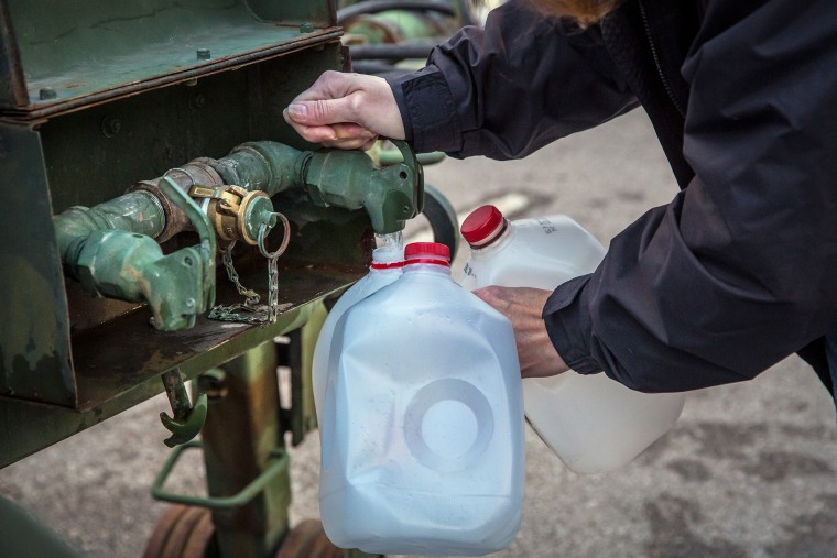 A local resident fills jugs with water at a distribution center in Charleston, W.Va., on Jan. 12, 2014.