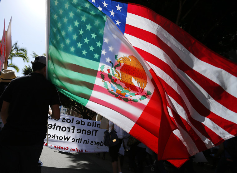 A young man carries national flags of the U.S. and Mexico through the streets during a May Day march, May 1, 2013, in San Diego, Calif.