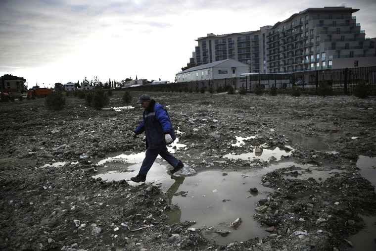 A construction worker steps over a puddle in a lot being prepared to be turned into a grassy lawn on Feb. 6, 2014, in Sochi, Russia.