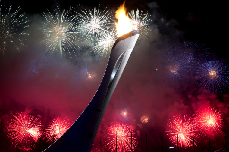 Fireworks explode behind the Olympic torch after it was lit at end of the opening ceremony for the 2014 Winter Olympics in Sochi, Russia, Feb. 7, 2014.