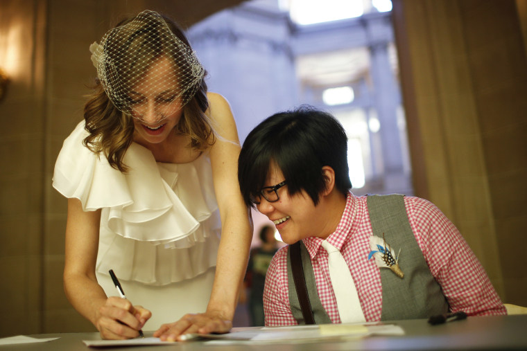 Ashlee Meyer (L) and partner KY Choi (R) sign their marriage license as they prepare to get married, June 29, 2013 at City Hall in San Francisco, Calif.