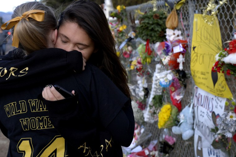 Seniors Lexi Barrent, right, and Melissa Tombaugh embrace outside Arapahoe High School in Centennial, CO Dec. 19, 2013