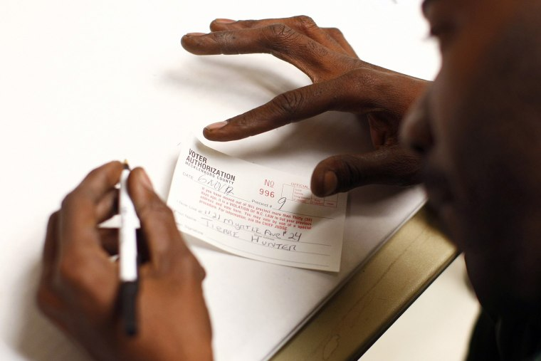 A man fills out a voter authorization form as he arrives to vote in Charlotte, North Carolina, Nov. 6, 2012.