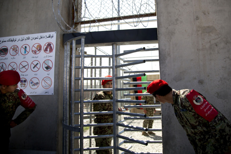 Afghan National Army soldiers peek through the gate of the Parwan Detention Facility in Bagram, Afghanistan, on March 25, 2013.