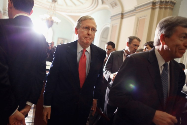 Senate Minority Leader Mitch McConnell (R-KY) (C) leaves after talking with reporters at the U.S. Capitol on Jan. 28, 2014 in Washington, DC.