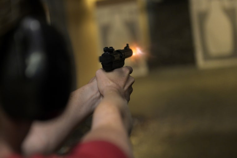 A woman fires her handgun during a Multi-State Concealed Carry class at a shooting range in Centennial, CO July 27, 2013.