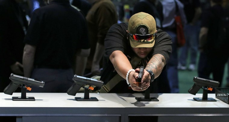 Firearms buyer Joshua Asperila checks out various Glock hand guns on display during the Shooting Hunting and Outdoor Trade Show,  Tuesday, Jan. 14, 2014, in Las Vegas.