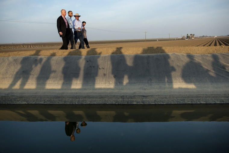 From left, California Governor Jerry Brown and President Barack Obama are lead on a tour of Empresas Del Bosque, Inc.'s farm by Joe Del Bosque and Maria Gloria Del Bosque, Feb. 14, 2014 in Los Banos, Calif.