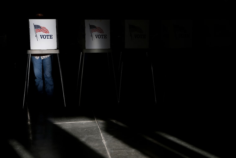Voting booths are illuminated by sunlight as voters cast their ballots at a polling place, Nov. 6, 2012, in Billings, Mont.