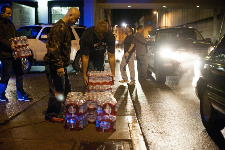 Lines of cars formed around the block as pallets of bottled water were being brought and distributed in downtown Charleston, West Virginia, Jan. 10, 2014.