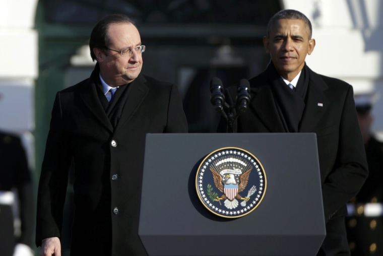French President Francois Hollande (L)  looks over at U.S. President Barack Obama during a State Arrival ceremony in Hollande's honor on the South Lawn of the White House in Washington, February 11, 2014.