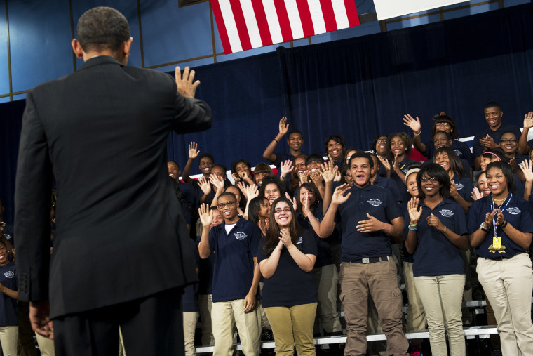 Barack Obama waves to students prior to speaking at Hyde Park Academy in Chicago, Feb. 15, 2013.