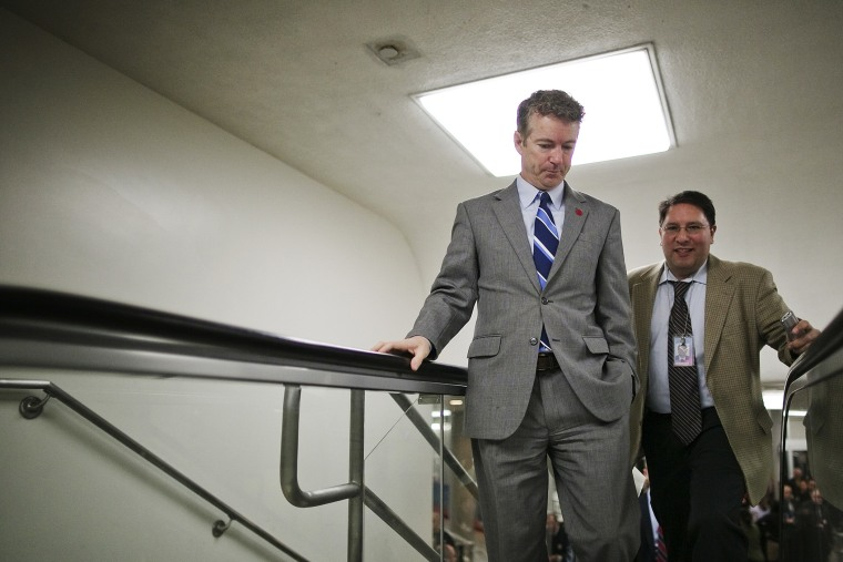 U.S. Senator Rand Paul talks to a reporter as he arrives for the weekly Republican caucus luncheon at the U.S. Capitol, Feb. 4, 2014.