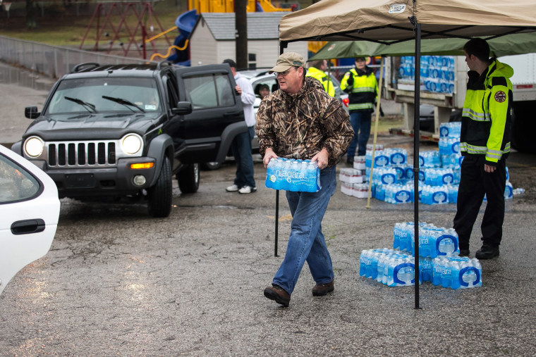Members of the Nitro Volunteer Fire Department help to distribute bottled water to local residents Saturday Jan. 11, 2014.