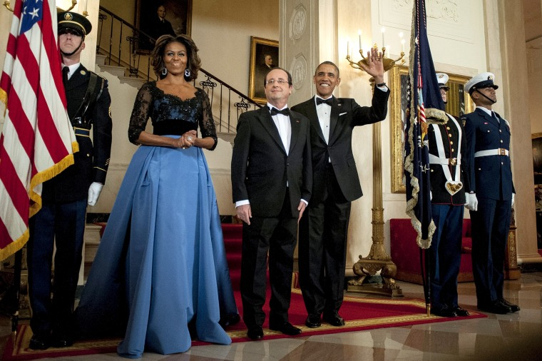 US President Barack Obama and First Lady Michelle Obama pose for a photo with President Francois Hollande of France on the Grand Staircase in the White House in Washington on Feb. 11, 2014.