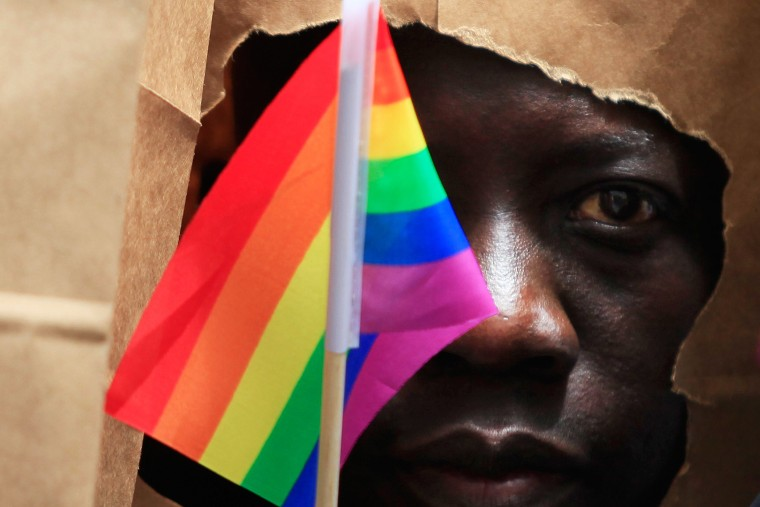 An asylum seeker from Uganda covers his face with a paper bag in order to protect his identity as he marches with the LGBT Asylum Support Task Force during the Gay Pride Parade in Boston, Mass. on June 8, 2013.