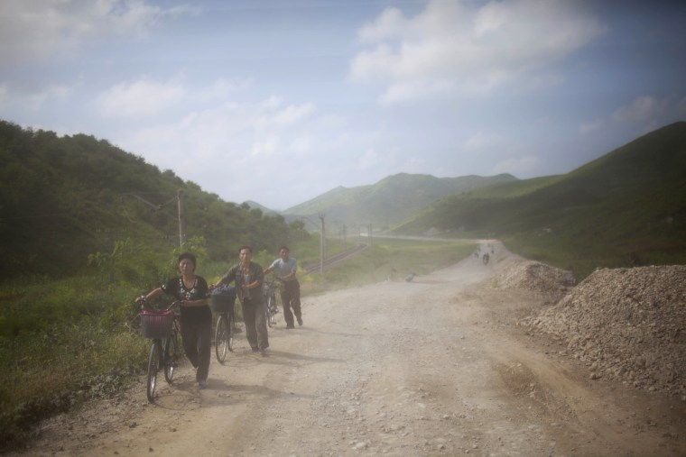 North Koreans are dusted by passing vehicles as they push their bicycles down a dirt road in Songchon County, North Korea on Aug 13, 2012.
