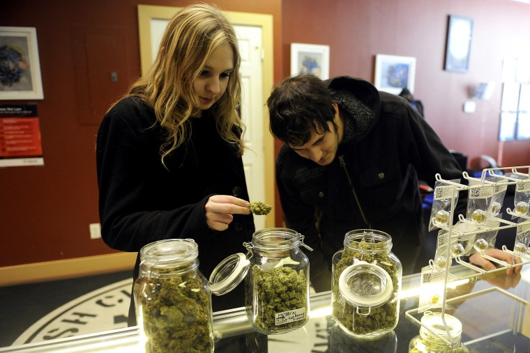 Austin Labry and Kelsey K. check out the selection of wax and shatters at Denver Kush Club, Jan. 1, 2014.