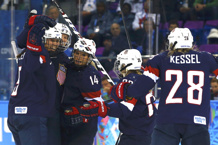 Team USA's Kacey Bellamy (2nd from L) is congratulated by teammates after scoring against Sweden during the first period of their women's semi-final ice hockey game at the 2014 Sochi Winter Olympics, Feb. 17, 2014.