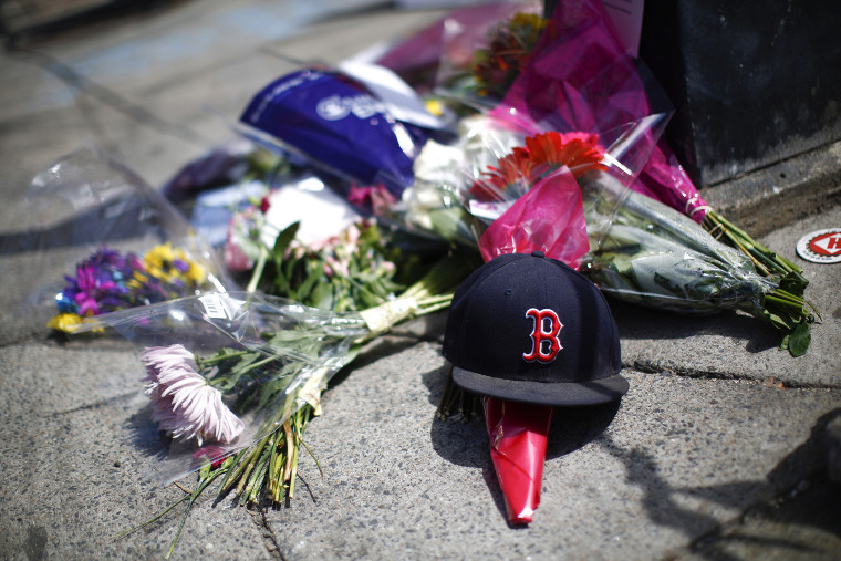 A makeshift memorial on the sidewalk on Newbury Street near the site of two bomb explosions that occurred during the Boston Marathon, April 18, 2013.