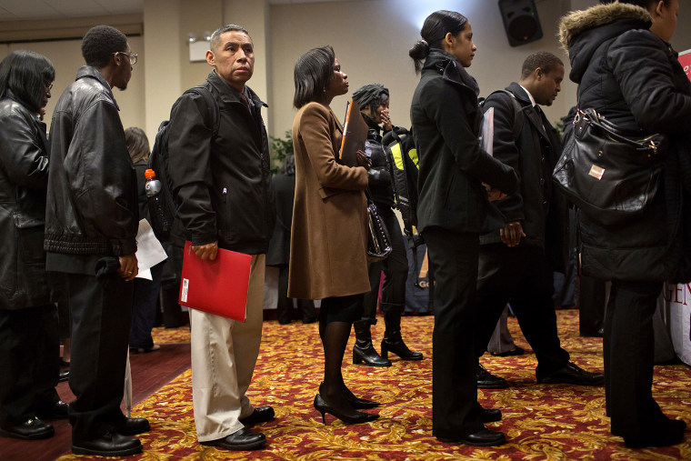 Job seekers wait to talk to recruiters and fill out applications at a job fair in New York, U.S., on Jan. 16, 2014.