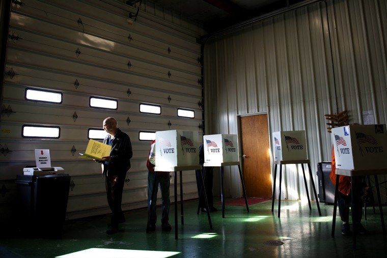 Voters cast ballots at a polling station at Ray Lounsberry's shed in Nevada Township, Iowa on Election Day, Nov. 6, 2012