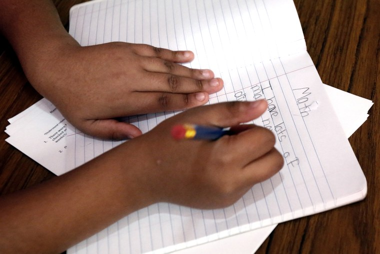 A student writes in a notebook.