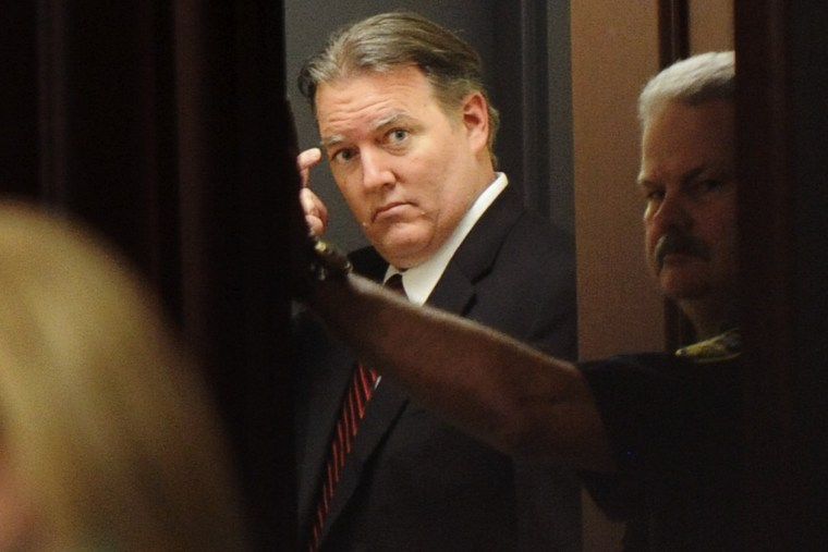 Michael Dunn stands and looks back into the courtroom from the holding area after the verdicts were announced in his trial in Jacksonville, Florida Feb. 15, 2014.
