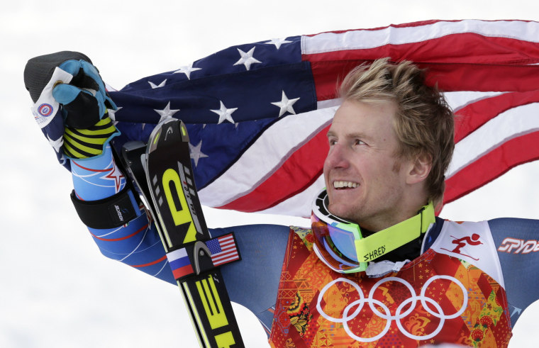 Men's giant slalom gold medalist Ted Ligety of the United States poses for photographers with the American flag on the podium at the Sochi 2014 Winter Olympics, Feb. 19, 2014, in Krasnaya Polyana, Russia.