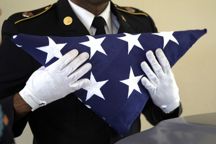 An Army National Guardsman, holds an American flag during a funeral.