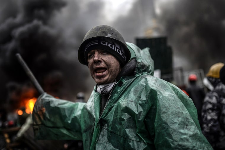 A protester stands behind barricades during clashes with police on February 20, 2014 in Kiev.
