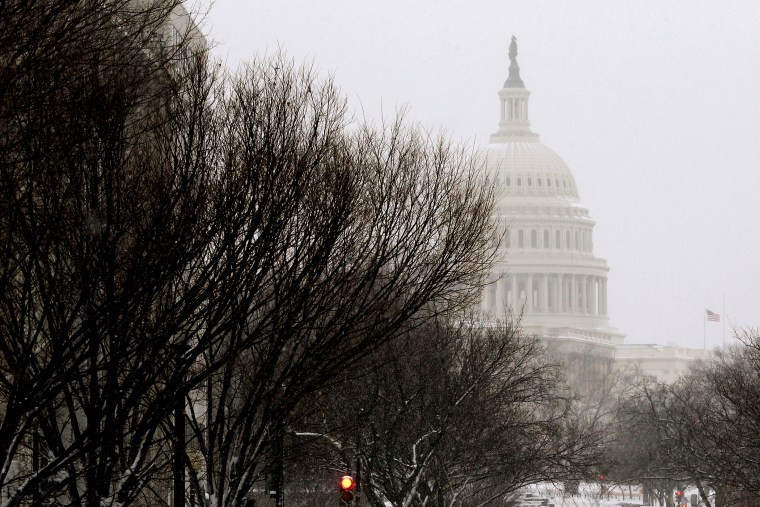 A pedestrian walks across New Jersey Avenue in front of the U.S. Capitol building.