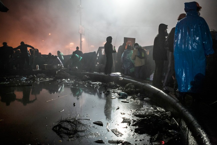 Anti-government demonstrators stand behind a barricade near Kiev's Independence Square on Feb. 19, 2014.