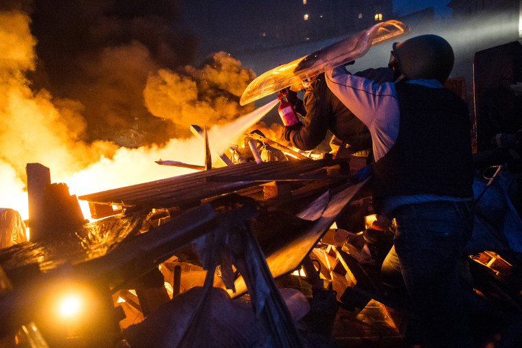 Anti-government protesters stand behing their burning barricades during clashes with police in the center of Kiev.