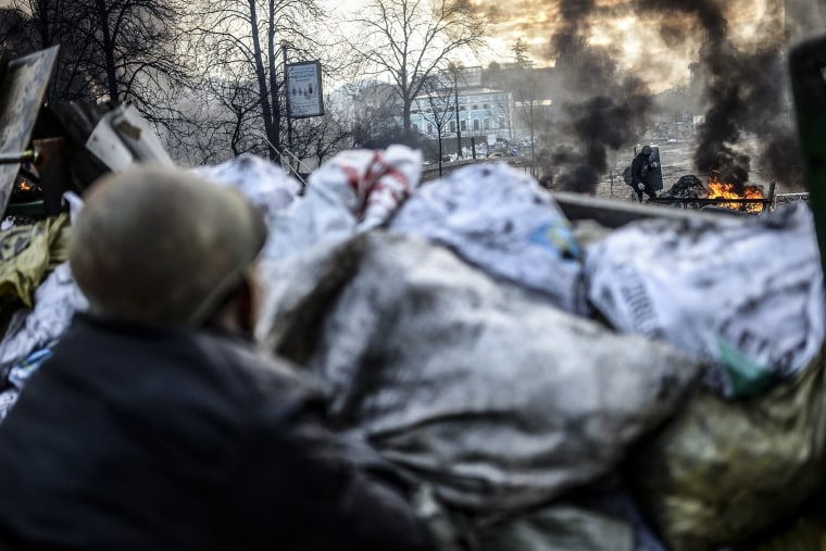 An anti-government protester looks at a protester adding tires to a fire at a barricade on February 21, 2014 in Kiev.