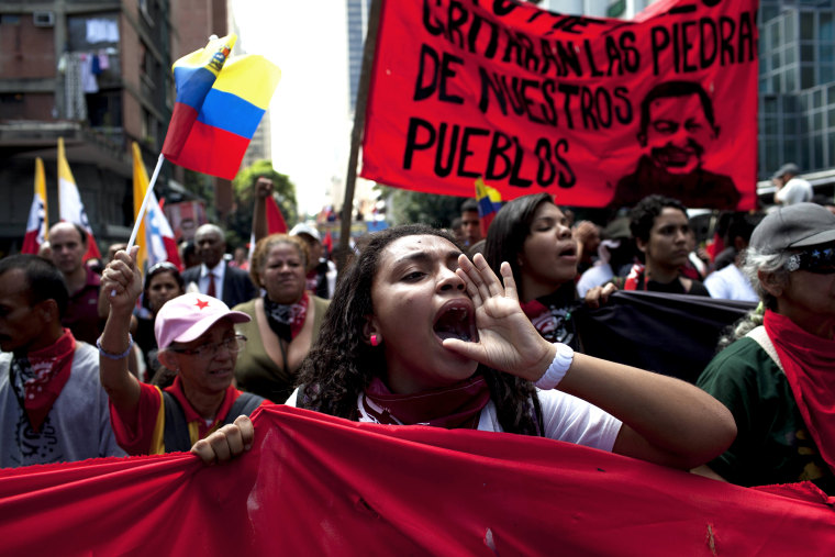 """Members of a pro-government \""""colectivo,\"""" or \""""collective,\"""" march in downtown Caracas, Venezuela, on  Feb. 20, 2014."""