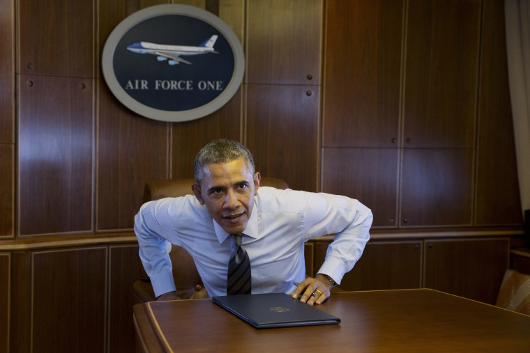 President Barack Obama prepares to walk away from a table, Wednesday, Feb. 19, 2014, in a conference room in flight aboard Air Force One.