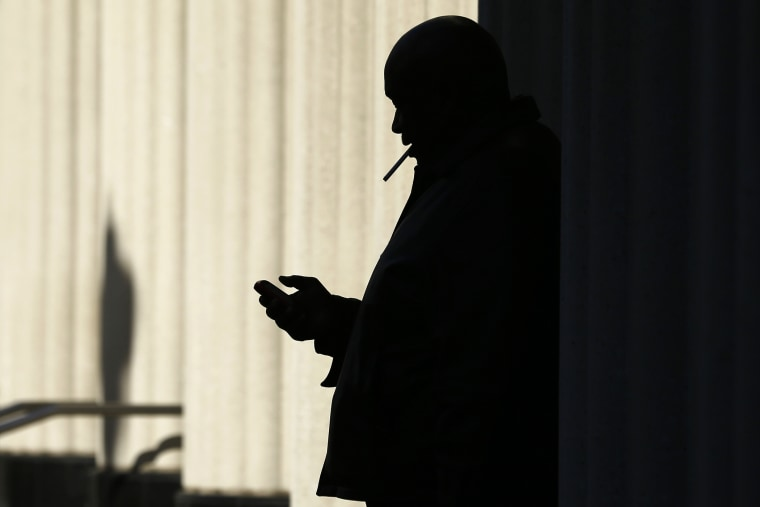 A man on his mobile phone as he smokes a cigarette outside, Dec. 9. 2013, in San Diego, Calif.