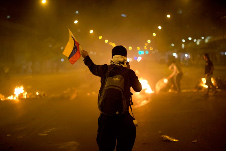 An anti-government demonstrator holds a representation of Venezuela's national flag in front of a burning barricade, Feb. 21, 2014, in the Altamira neighborhood of Caracas, Venezuela.