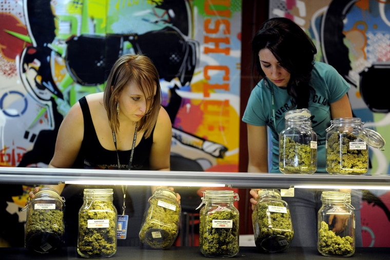 Brittany Zewe, left, and Jess Vanderpool take jars of different strains of marijuana off the counter between customers at Denver Kush Club in Denver, Colorado on Jan. 1, 2014.