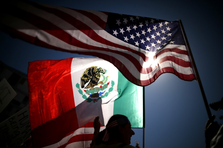 Protesters carry American and Mexican flags on their march to demand immigration reform in Los Angeles, California, October 5, 2013.