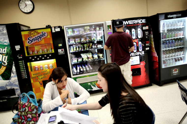 A student selects baked potato chips from a vending machine at Commack High School in Commack, N.Y., Sept. 19, 2011.