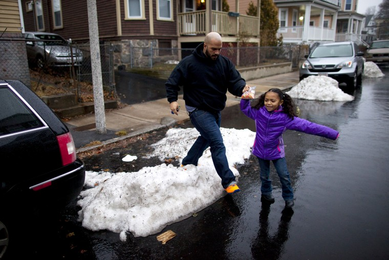 Yasmani Santiago, 32, of Dorchester, walks his daughter to the car, Dec. 23, 2013. Santiago is one of the tens of thousands of Massachusetts residents who prepared to lose their unemployment benefits on Dec. 28th.
