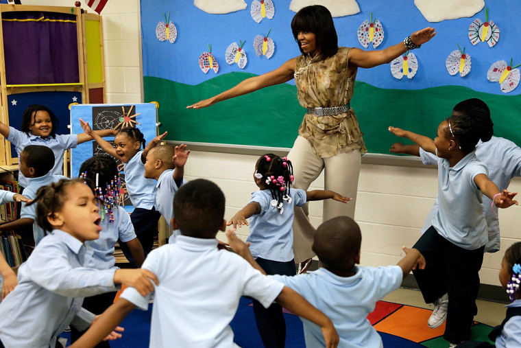 U.S. first lady Michelle Obama dances with pre-kindergarten students while she visits the Savoy School in D.C., May 24, 2013.