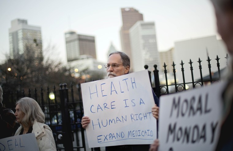 Bert Skellie, of Decatur, Ga., protests for Medicaid expansion outside the Wild Hog Supper, Sunday, Jan. 12, 2014, in Atlanta.