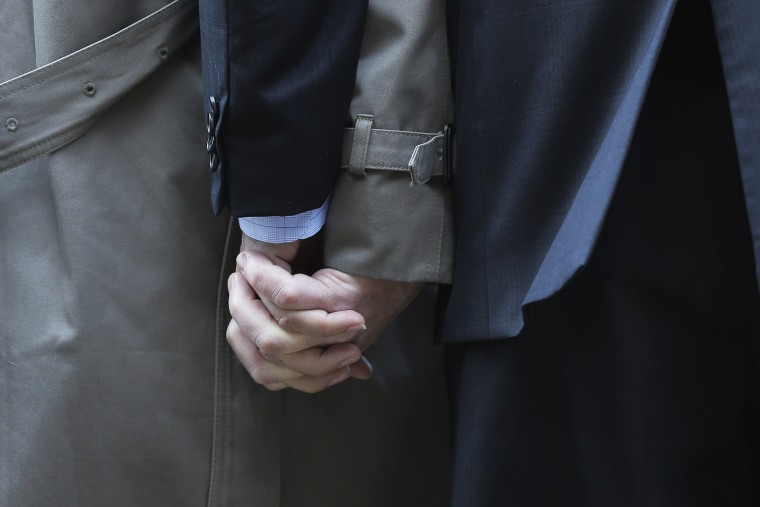 Mark Phariss, left, clutches the hand of partner Victor Holmes, right, as they talk to the media outside the U.S. Federal Courthouse in San Antonio, Texas, Feb. 12, 2014.