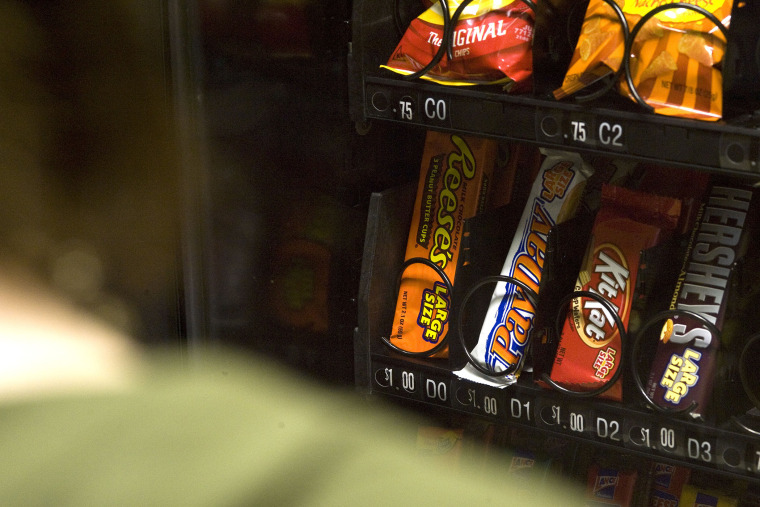 A stutdent stands in front of a vending machine in Charleston, W.Va.