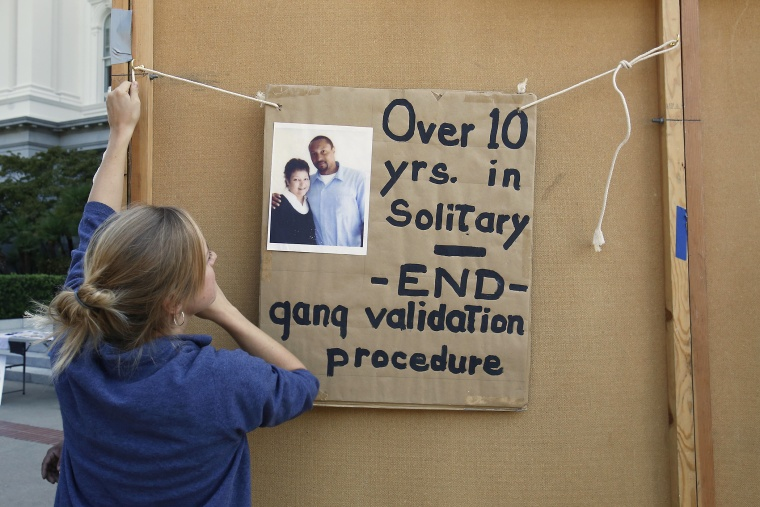 Georgia Valentine hangs a poster calling for reform in the use of solitary confinement in California prisons, Oct. 9, 2013.