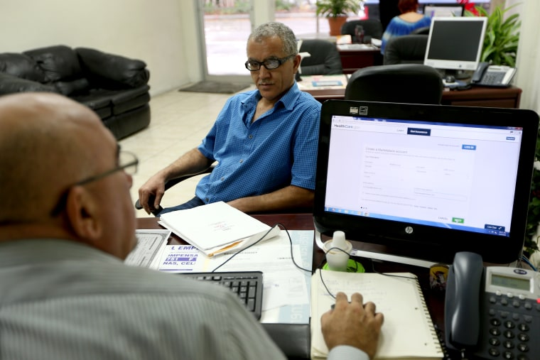 Hisham Uadadeh enrolls in a health insurance plan under the Affordable Care Act with the help of A. Michael Khoury in Miami, Feb. 13, 2014.
